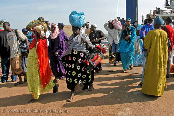 people leaving the Banjul ferry wearing traditional dress