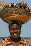 woman carrying a wicker basket with souvenirs on her head