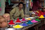 man selling color dyes at the market