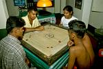 young men playing a board game, finger pool