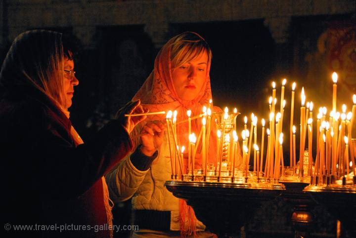 Pictures of Ukraine - women burning candles,  Caves Monastery, Kyiv (Kiev)