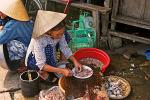 woman with straw hat selling shrimps and crabs