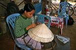 woman making a traditional straw hat